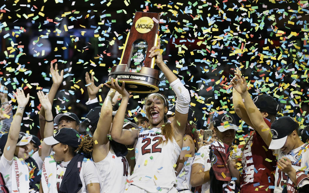 South Carolina forward A'ja Wilson (22) holds the trophy as she and her teammates celebrate a win over Mississippi State in the final of NCAA women's Final Four college basketball tournament, Sund ...