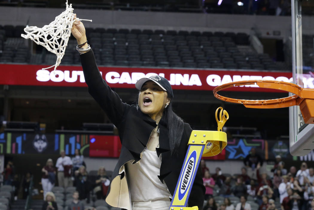 South Carolina coach Dawn Staley cuts down the net as she and the team celebrate their win over Mississippi State in the final of NCAA women's Final Four college basketball tournament, Sunday, Apr ...