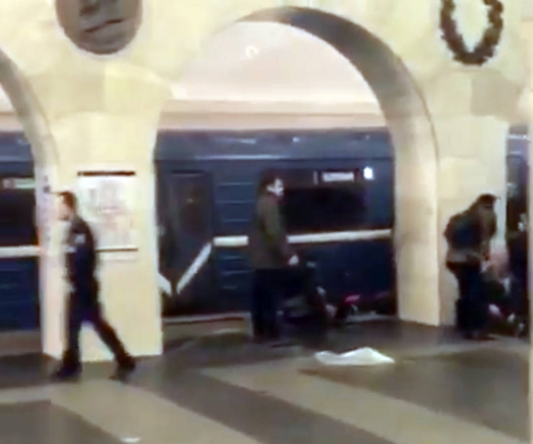 In this grab taken from AP video, Russian police officer, left, and people walk past the damaged train at the Tekhnologichesky Institut subway station in St.Petersburg, Russia, Monday, April 3, 20 ...