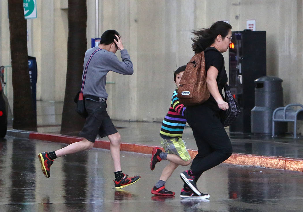 Pedestrians run for cover during the afternoon rain on Monday, April 3, 2017, in Las Vegas. (Bizuayehu Tesfaye/Las Vegas Review-Journal) @bizutesfaye