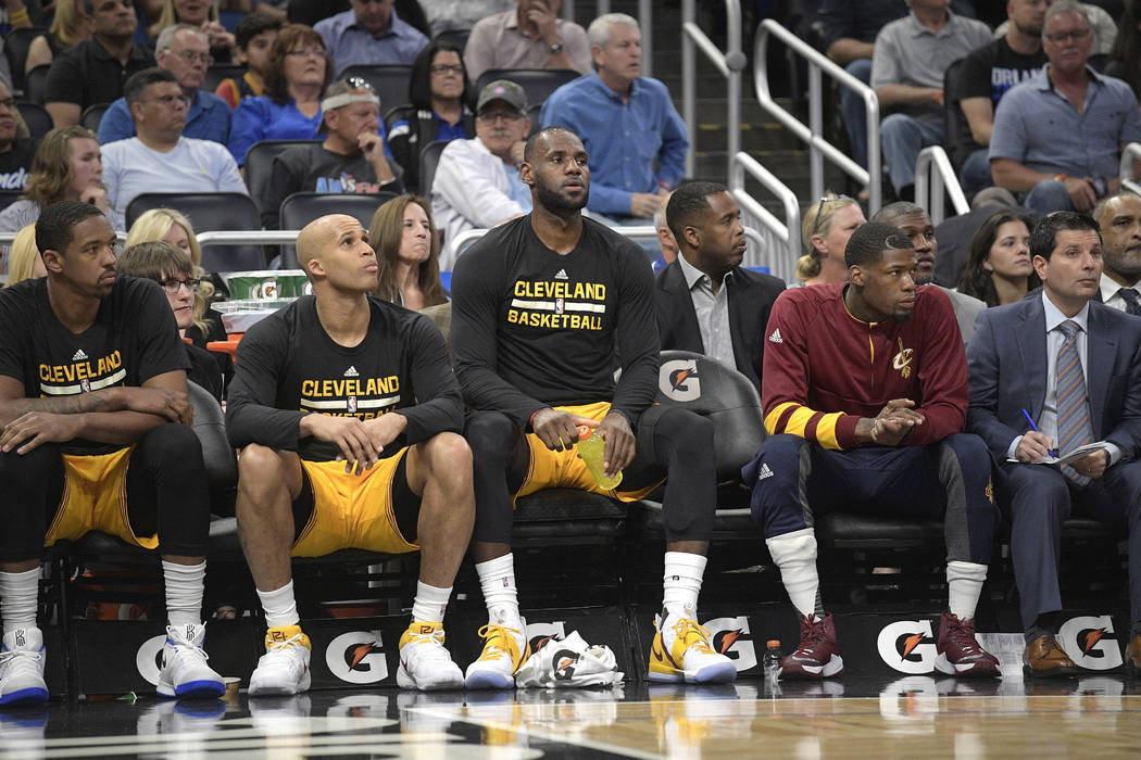 Cleveland Cavaliers forward LeBron James, center, rests on the bench during the first half of an NBA basketball game against the Orlando Magic in Orlando, Fla., Saturday, March 11, 2017. (AP Photo ...