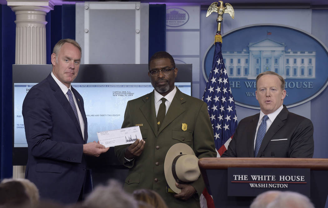 Interior Secretary Ryan Zinke, left, and Harpers Ferry National Historic Park Superintendent Tyrone Brandyburg, accompanied by White House press secretary Sean Spicer, hold up a check during the d ...