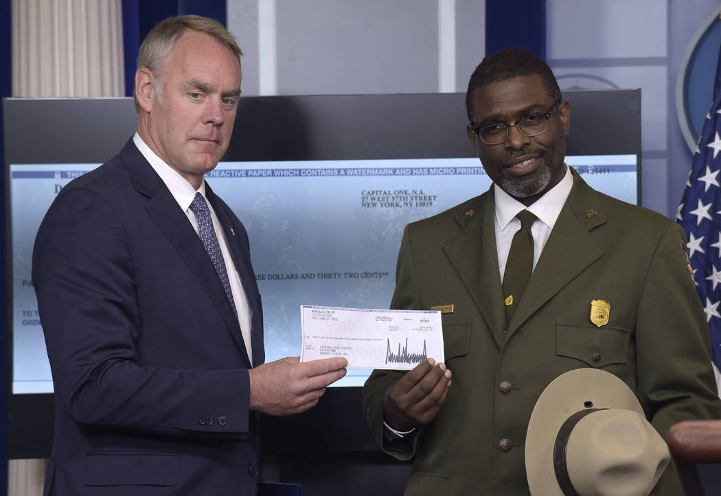 Interior Secretary Ryan Zinke, left, and Harpers Ferry National Historic Park Superintendent Tyrone Brandyburg, hold up a check during the daily briefing at the White House in Washington, Monday,  ...