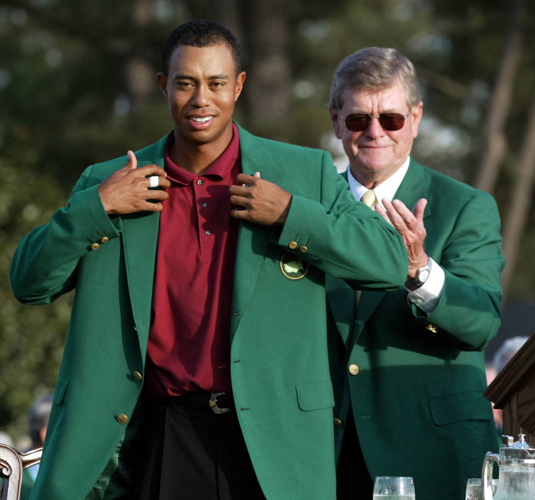 "FILE - In this April 14, 2009, file photo, Tiger Woods, left, adjusts the 2002 Masters green jacket as Augusta National Golf Club chairman William W.""Hootie"" Johnson applauds at  ..."