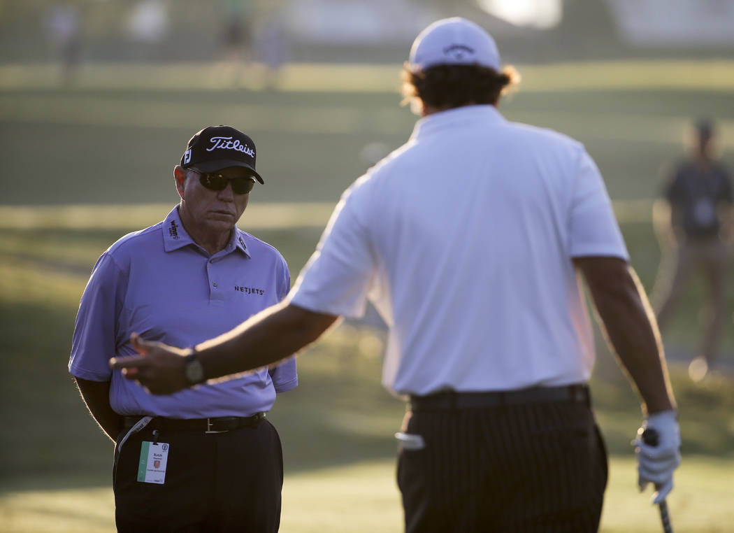 Phil Mickelson, right, talks with Butch Harmon on the practice green before a practice round for the U.S. Open golf tournament in Pinehurst, N.C., Tuesday, June 10, 2014. The tournament starts Thu ...