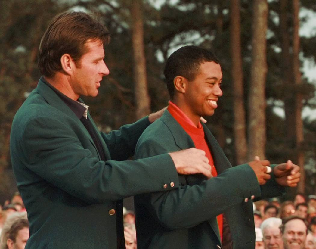 1997 Masters champion Tiger Woods receives his Green Jacket from last year's winner Nick Faldo, left, at the Augusta National Golf Club in Augusta, Ga., Sunday, April 13, 1997. (AP Photo/Amy Sance ...