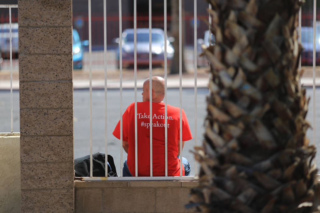 A man smokes a cigarette while sitting on a wall at The Giving Project, an event designed to help those in need, at 1401 Las Vegas Blvd. North on Saturday, April 8, 2017. (Brett Le Blanc/View) @bl ...