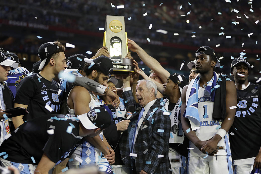 North Carolina head coach Roy Williams is interviewed as his team celebrate after the finals of the Final Four NCAA college basketball tournament against Gonzaga, Monday, April 3, 2017, in Glendal ...