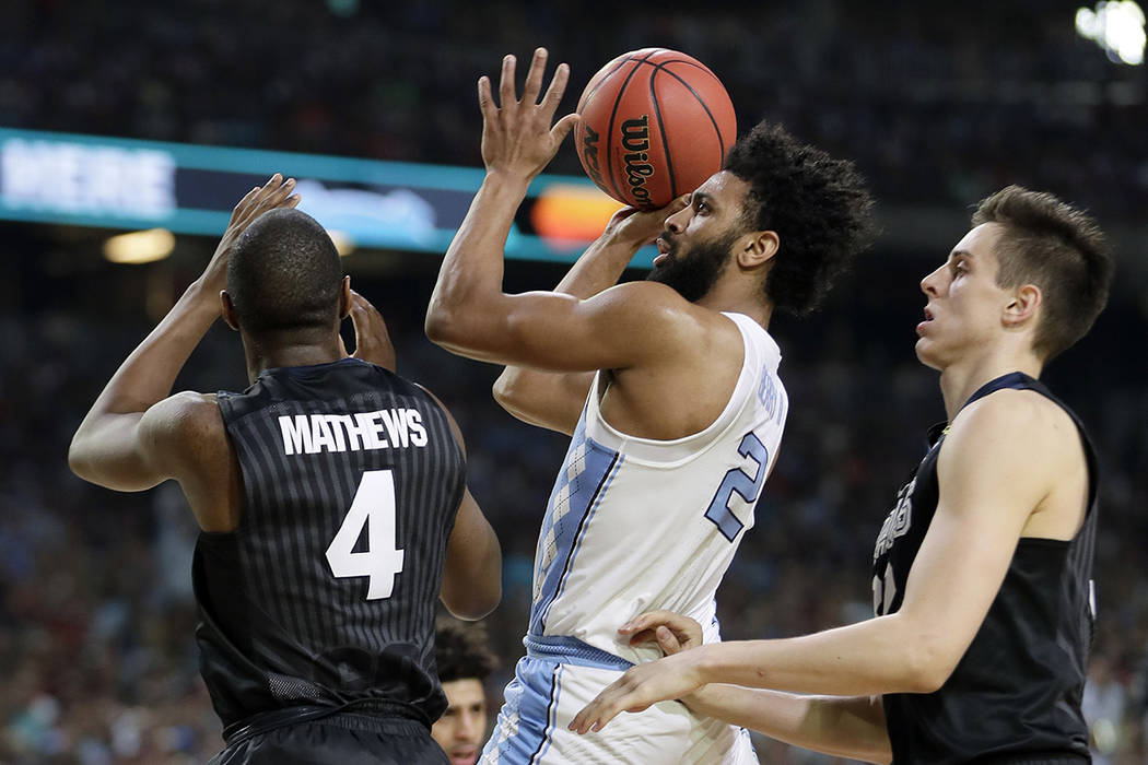 North Carolina's Joel Berry II (2) takes a shot between Gonzaga's Jordan Mathews (4) and Zach Collins during the first half in the finals of the Final Four NCAA college basketball tournament, Mond ...
