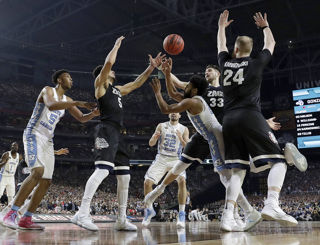 Gonzaga's Johnathan Williams (3) and Killian Tillie (33) block a shot by North Carolina's Joel Berry II (2) during the second half in the finals of the Final Four NCAA college basketball tournamen ...