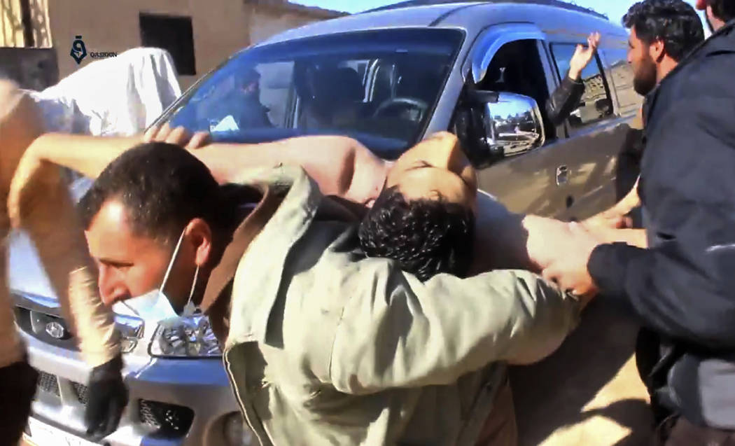 This frame grab from video provided on Tuesday April 4, 2017, shows a Syrian man carrying a man on his back who has suffered injuries from a suspected chemical attack, in the town of Khan Sheikhou ...