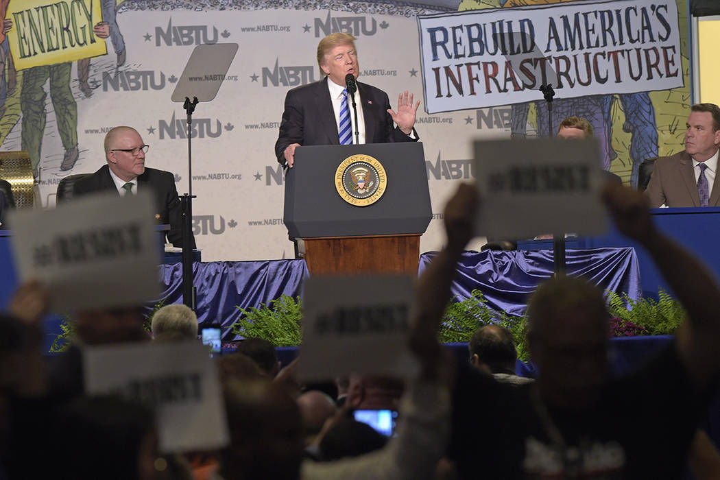 Protesters hold up signs as President Donald Trump speaks at the 2017 North America's Building Trades Unions National Legislative Conference in Washington, Tuesday, April 4, 2017. (AP Photo/Susan  ...