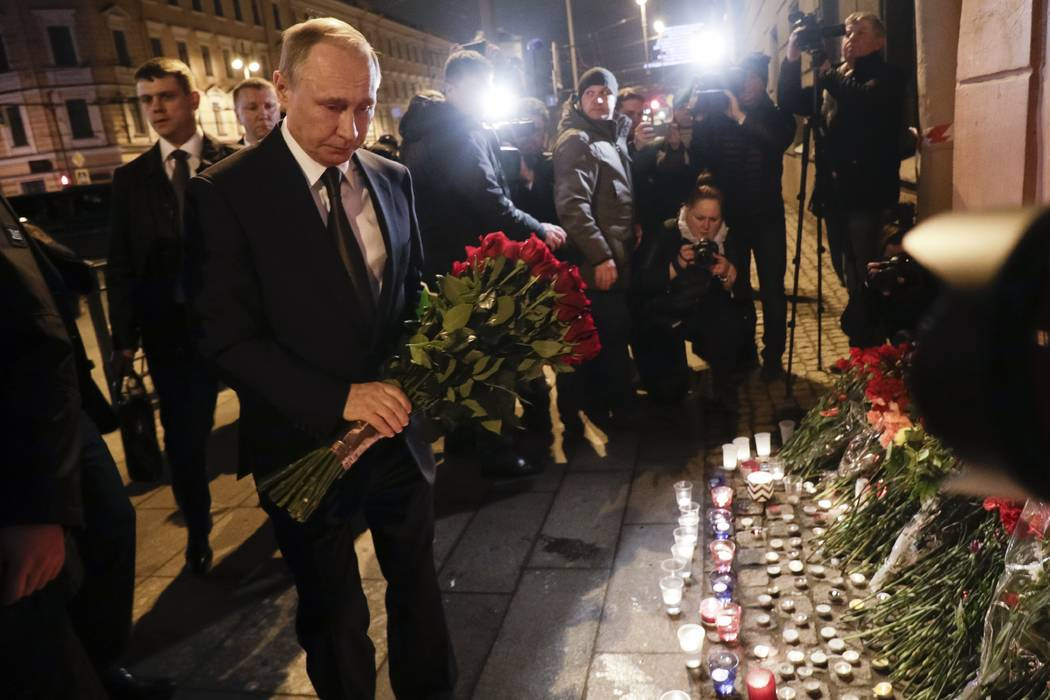 Russian President Vladimir Putin, left, lays flowers at a place near the Tekhnologichesky Institut subway station in St.Petersburg, Russia, Monday, April 3, 2017. (Dmitri Lovetsky/AP)