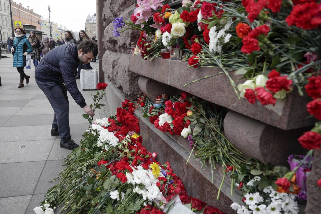 A man lays flowers at a symbolic memorial outside the Tekhnologichesky Institute subway station in St. Petersburg, Russia, Tuesday, April 4, 2017. (Dmitri Lovetsky/AP)