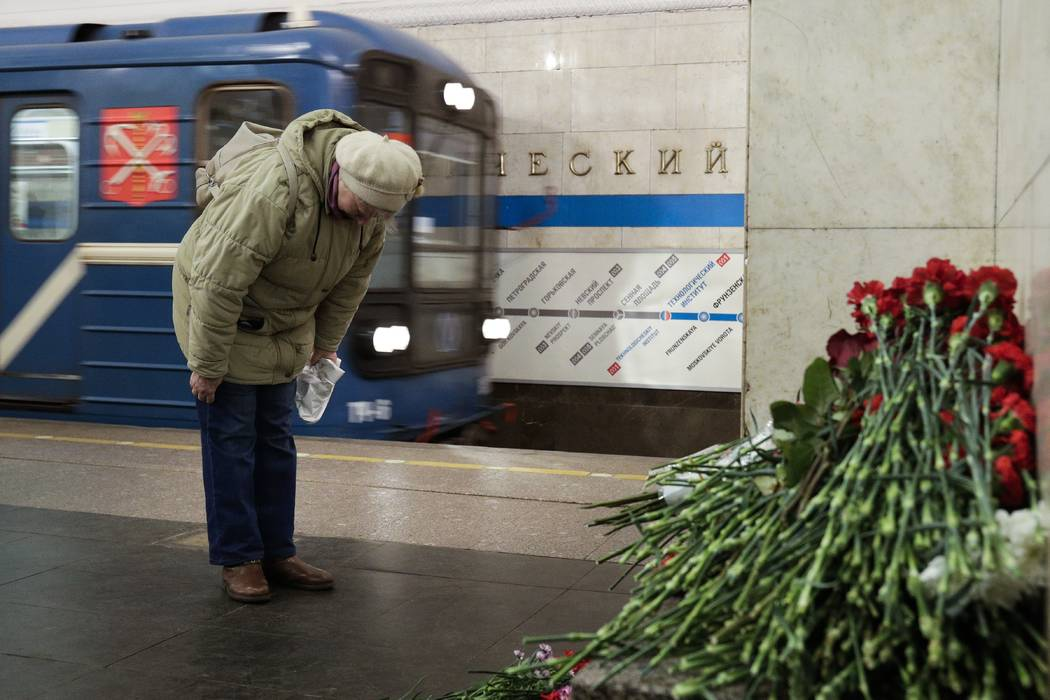 A woman pays her respects at a symbolic memorial at Tekhnologichesky Institute subway station in St. Petersburg, Russia, Tuesday, April 4, 2017. A bomb blast tore through a subway train deep under ...