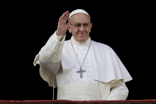"Pope Francis waves to faithful prior to delivering the Urbi et Orbi (Latin for ""to the city and to the world"") Christmas Day blessing from the main balcony of St. Peter's Basilica at the Vatican,  ..."