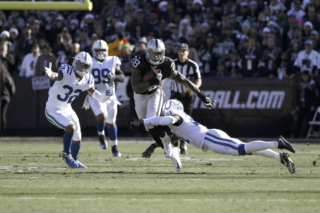 Oakland Raiders running back Latavius Murray (28) runs against Indianapolis Colts cornerback Vontae Davis (21) during the first half of an NFL football game in Oakland, California, on Dec. 24, 201 ...