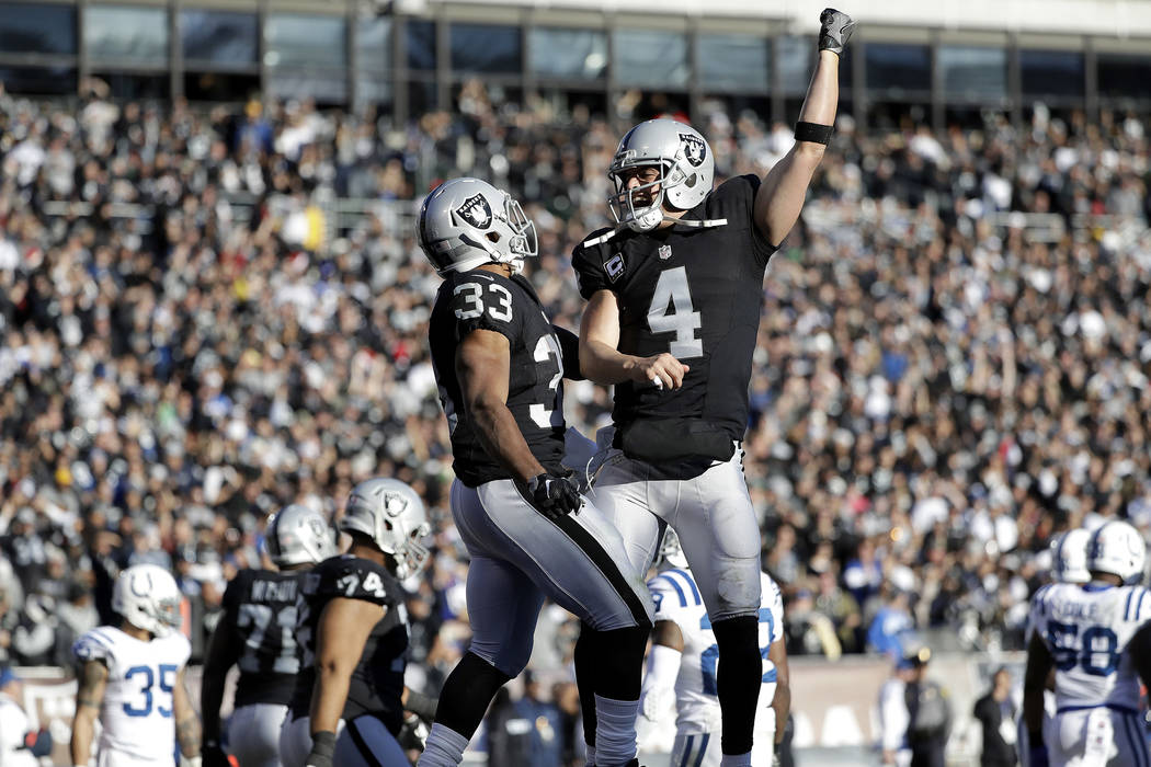 Oakland Raiders running back DeAndre Washington (33) celebrates after running for a touchdown with quarterback Derek Carr (4) during the second half of an NFL football game against the Indianapoli ...