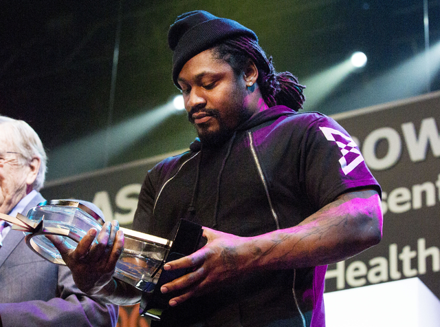 Marshawn Terrell Lynch, former American football running back, holds his trophy as he is enshrined in the Las Vegas Bowl Hall of Fame at the 25th Las Vegas Bowl Luncheon for the Houston Cougars an ...