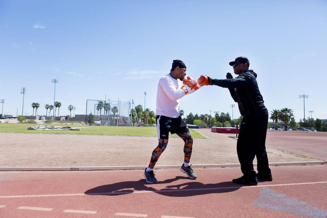 Boxer Shawn Porter, left, boxes with trainer Kenny Porter at the UNLV track in Las Vegas Monday, April 10, 2017. (Elizabeth Brumley Las Vegas Review-Journal) @EliPagePhoto