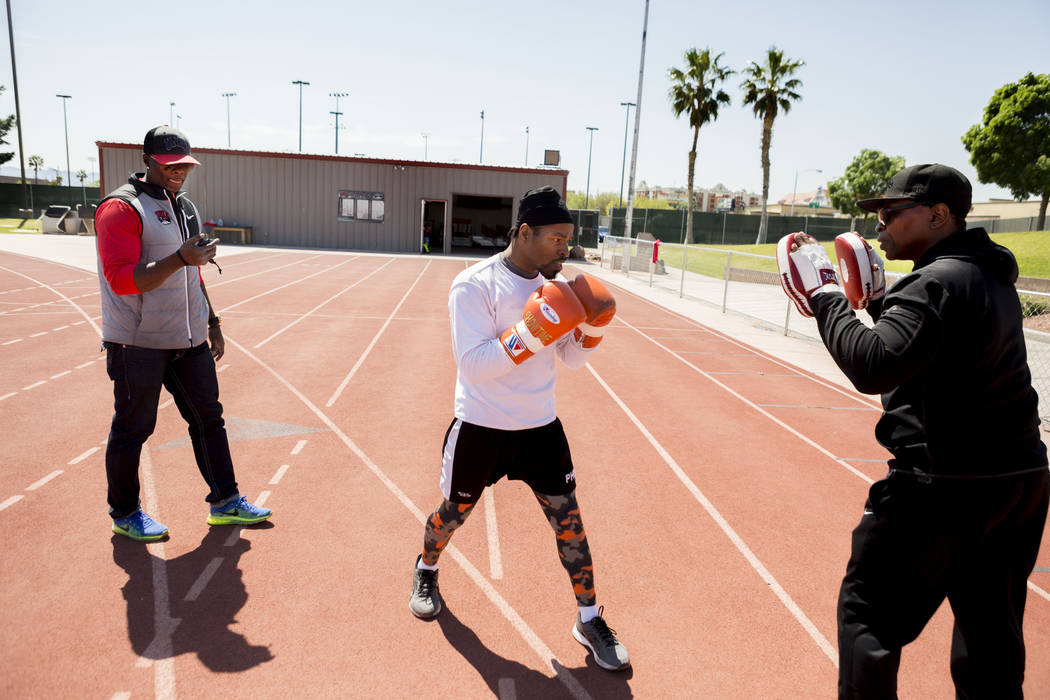 UNLV track and field coach Larry Wade, left, coaches professional boxer Shawn Porter, center, with trainer Kenny Porter at the UNLV track in Las Vegas Monday, April 10, 2017. Elizabeth Brumley Las ...