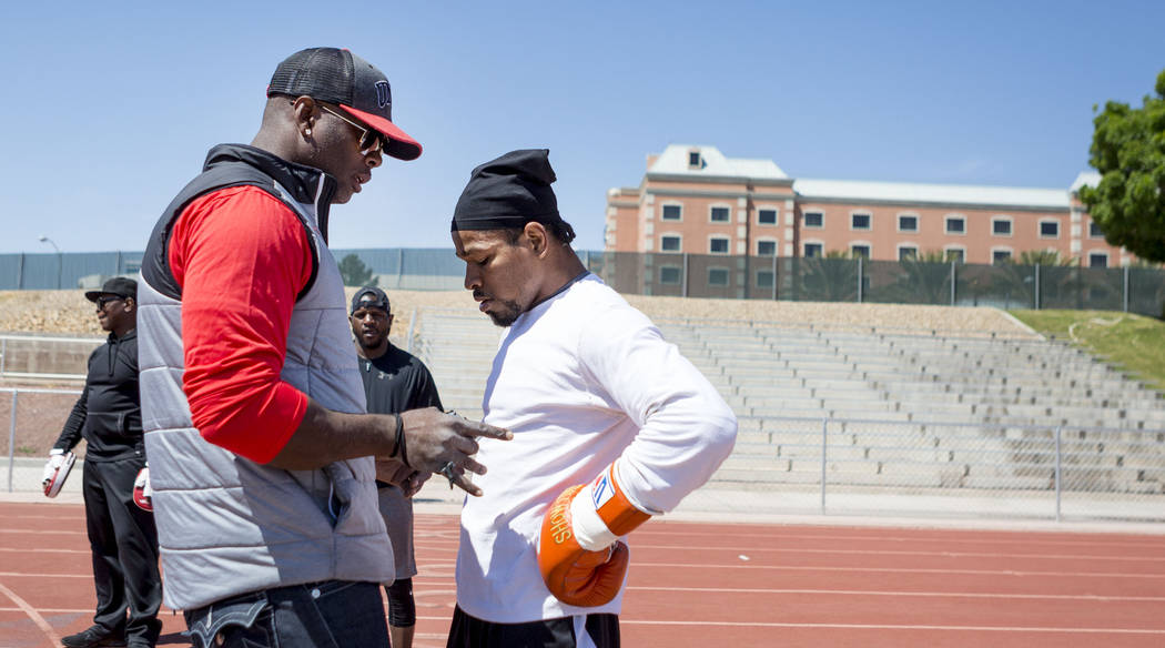 Larry Wade, UNLV track and field coach and Shawn Porter's strength and conditioning coach, left, speaks with Porter during a training session at the UNLV track in Las Vegas Monday, April 10, 2017. ...
