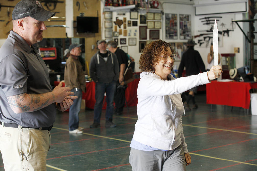 Chris Miller teaches Joyce Eisenberg how to throw a knife at the U.S. Nationals Pro/Am Knife & Tomahawk Championships  on Sunday, April 9, 2017, at the Superhero Foundry in Las Vegas. The even ...