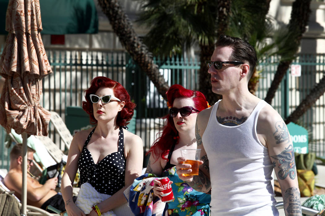 Dangelei Fox, left, Robin Nunnally and Tony Rabone of Seattle, Washington search for a poolside spot at the 19th Annual Viva Las Vegas Rockabilly Weekender at the Orleans Hotel and Casino on Satur ...