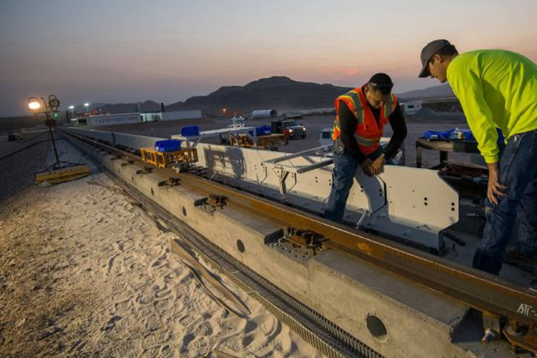 Hyperloop One workers install stator blocks at the test track and development site in North Las Vegas. (Hyperloop One)