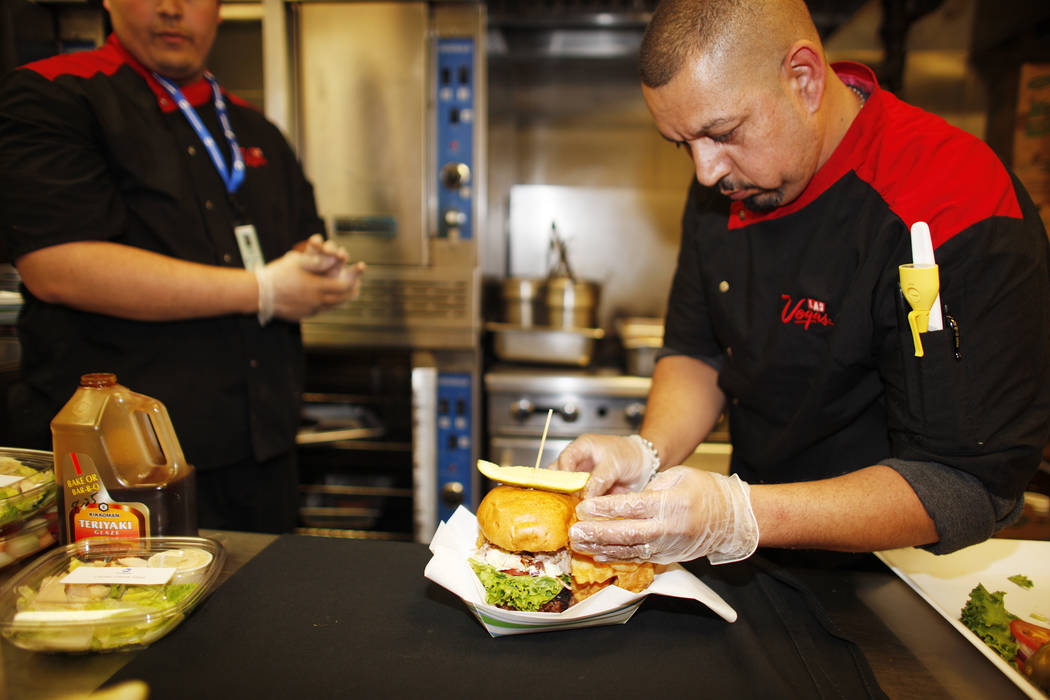 Lead Cook Isaac Mora and executive Chef Steve Almaraz top off a burger that will be sold under the new concessionaire, Centerplate, on Monday, April 10, 2017, at Cashman Field in Las Vegas. Rachel ...