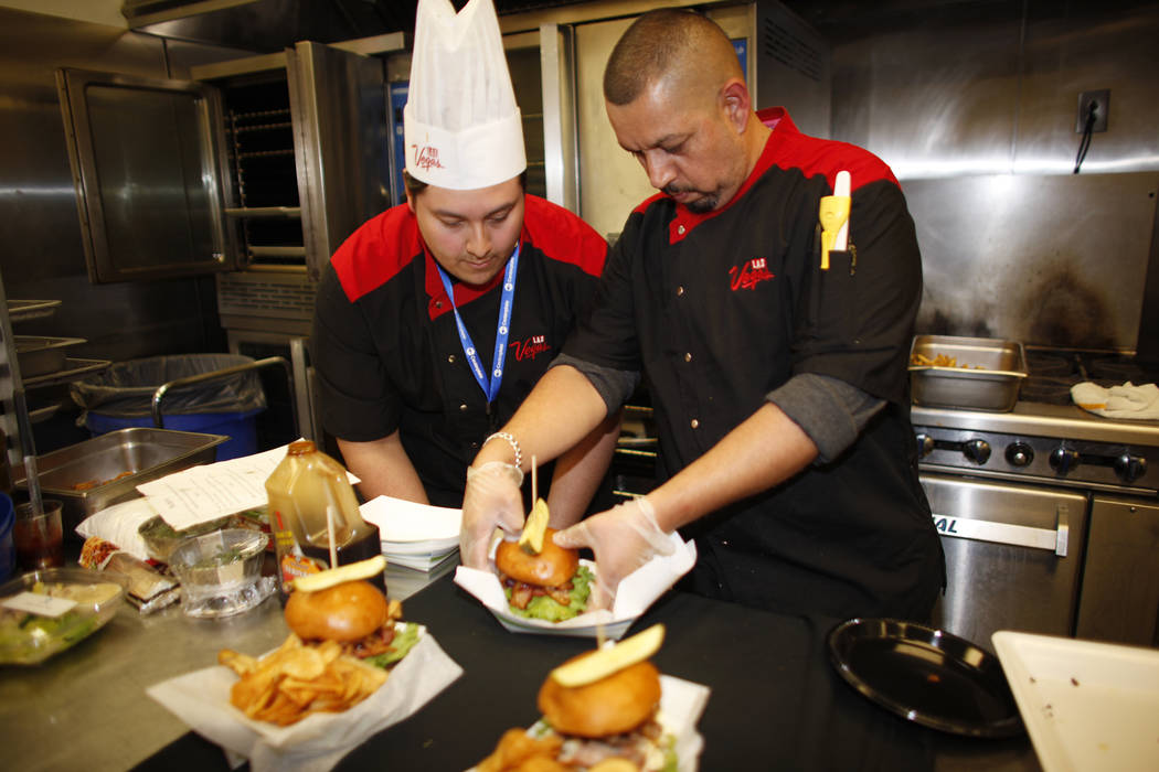 Lead Cook Isaac Mora and executive Chef Steve Almaraz put together a burger that will be sold under the new concessionaire, Centerplate, on Monday, April 10, 2017, at Cashman Field in Las Vegas. R ...
