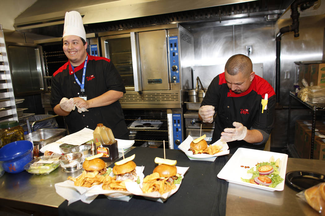 Lead Cook Isaac Mora and executive Chef Steve Almaraz put together new burgers that will be sold under the new concessionaire, Centerplate, on Monday, April 10, 2017, at Cashman Field in Las Vegas ...