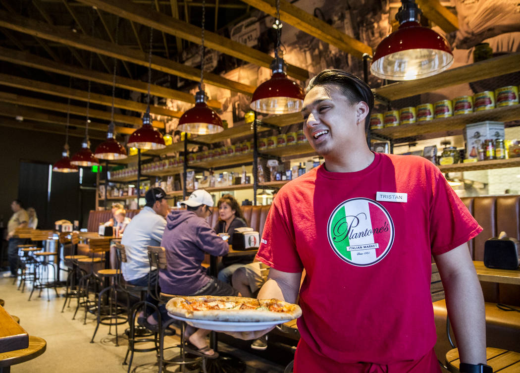 Server Tristan Alibangbang delivers a pizza to a guests table at Plantone's Italian Market on Saturday, April 8, 2017, in Las Vegas.  Benjamin Hager Las Vegas Review-Journal @benjaminhphoto
