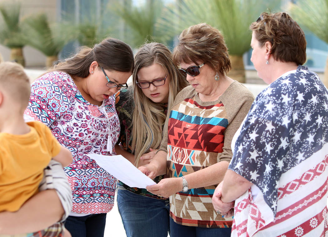 Carol Bundy, wife of rancher Cliven Bundy, second right, and her daughters Stetsy Cox, left, and Bailey Louge, second left, read the jury's verdict outside Lloyd George Federal Building on Monday, ...