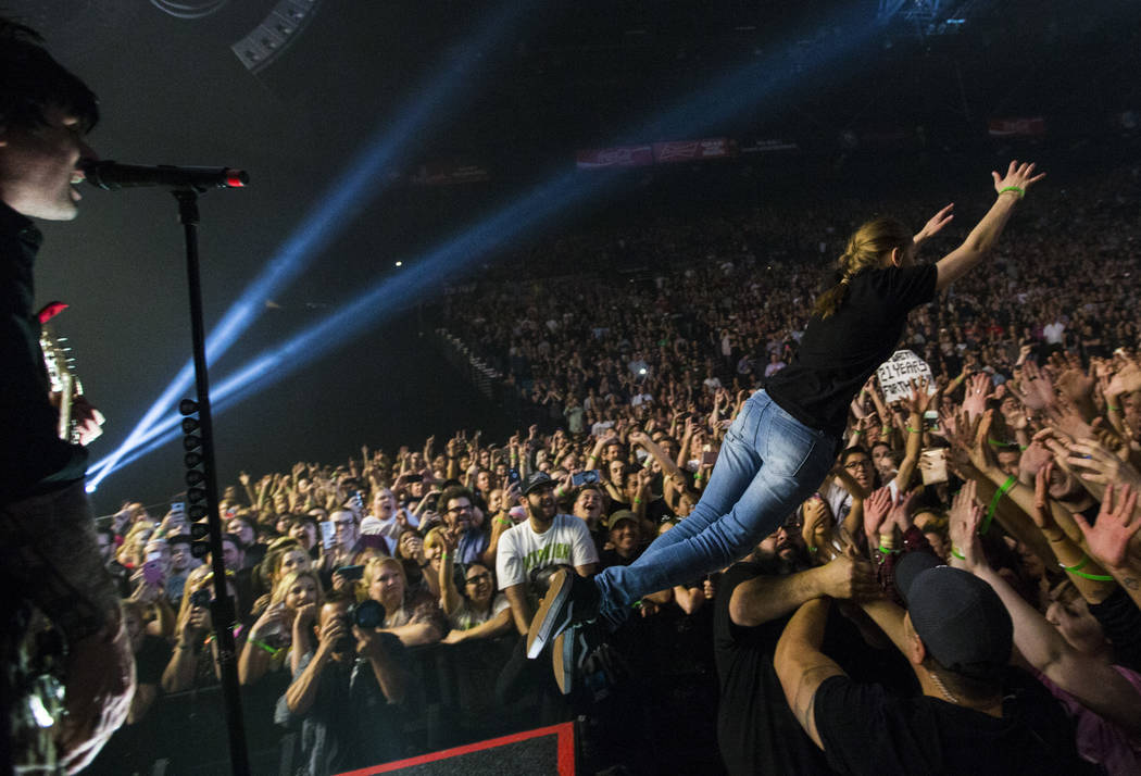 A fan who was brought on to stage dives into the crowd as Billie Joe Armstrong of Green Day, left, performs at the MGM Grand Garden Arena in Las Vegas on Friday, April 7, 2017. Chase Stevens Las V ...