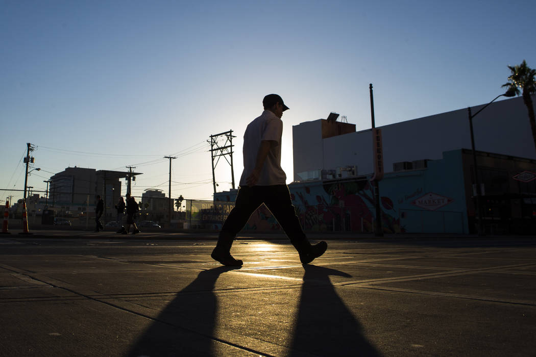 A man is silhouetted against the sun while walking along Fremont Street outside of the El Cortez hotel-casino in downtown Las Vegas. (Chase Stevens/Las Vegas Review-Journal)