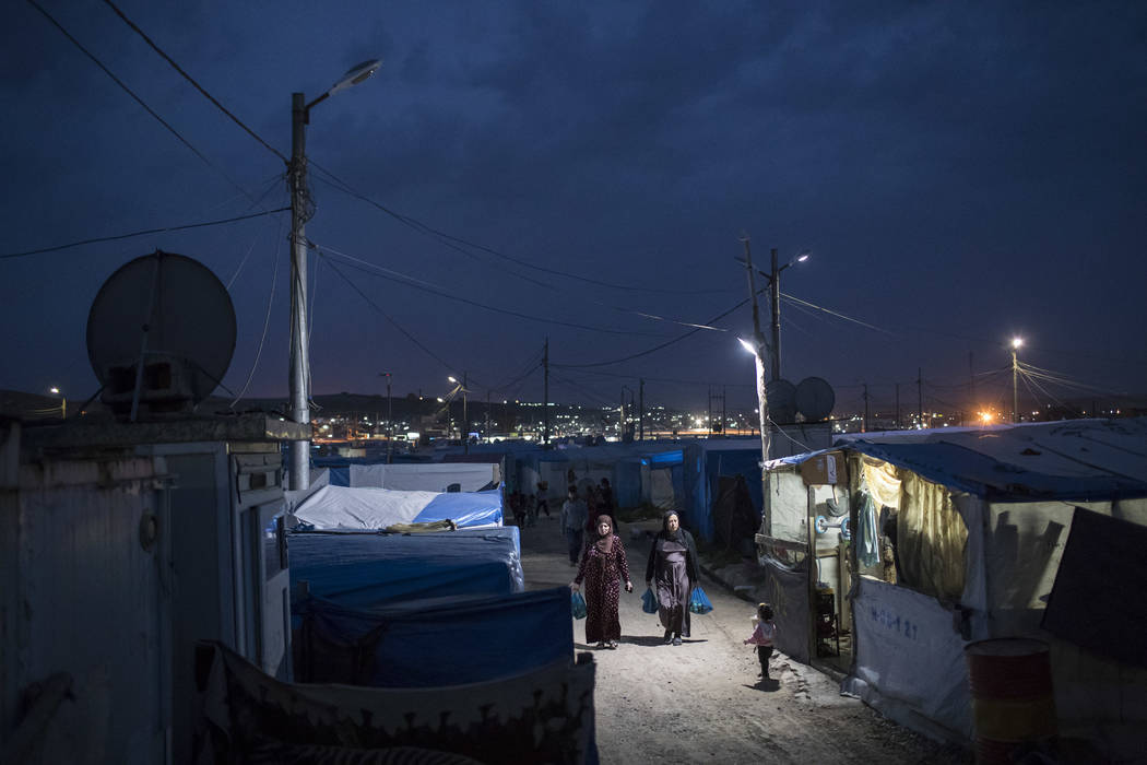 Syrian women walk at dusk in the Kawergosk refugee camp in northern Iraq, Saturday, April 8, 2017. For the millions of Syrian refugees scattered across camps and illegal settlements across the reg ...