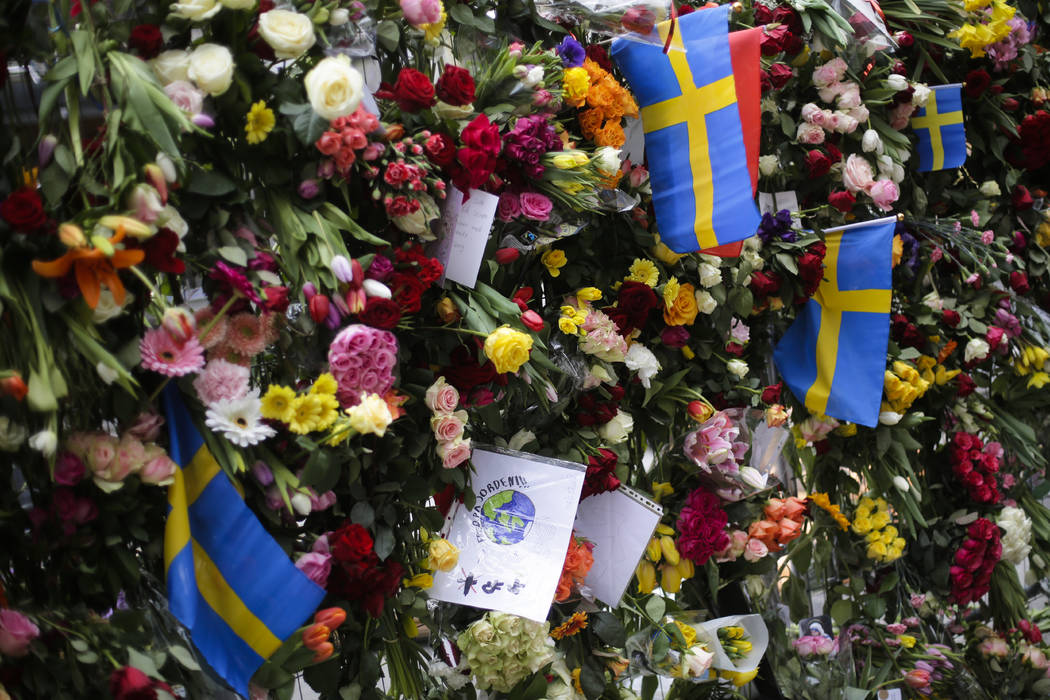 Swedish national flags placed between flowers in fence near the department store Ahlens following a suspected terror attack in central Stockholm, Sweden, Saturday, April 8, 2017. (Markus Schreiber/AP)
