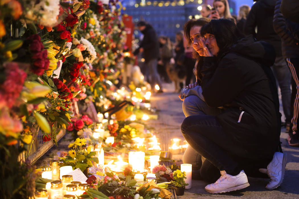 Two women mourn after they placed flowers on a fence near the department store Ahlens on Saturday, April 8, 2017, following Friday's suspected terror attack in central Stockholm, Sweden. Swedish p ...