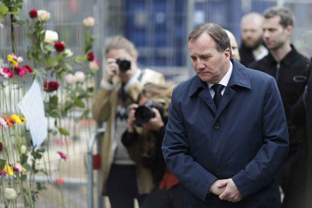 Sweden's Prime Minister Stefan Lofven stands at a fence near the department store Ahlens following a suspected terror attack in central Stockholm, Sweden, Saturday, April 8, 2017. (Markus Schreibe ...