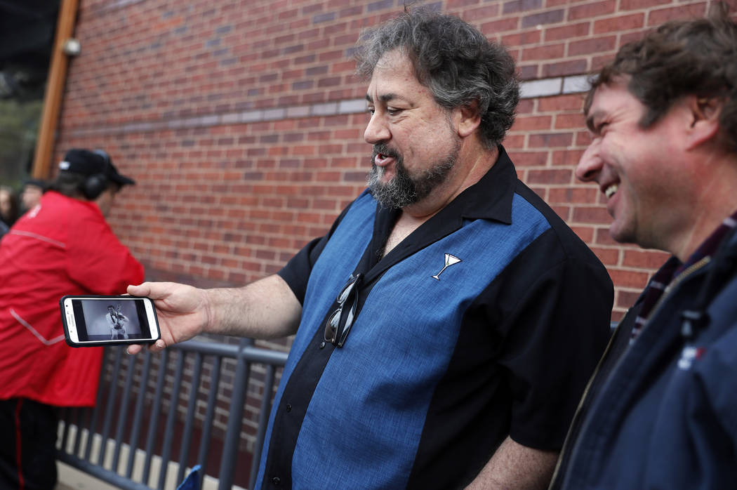 Alan Bozich, left, holds up his phone to watch a video of Chuck Berry as he stands in line with Jimmy Herrmann, right, to pay their respects to the rock 'n' roll legend during Berry's public viewi ...