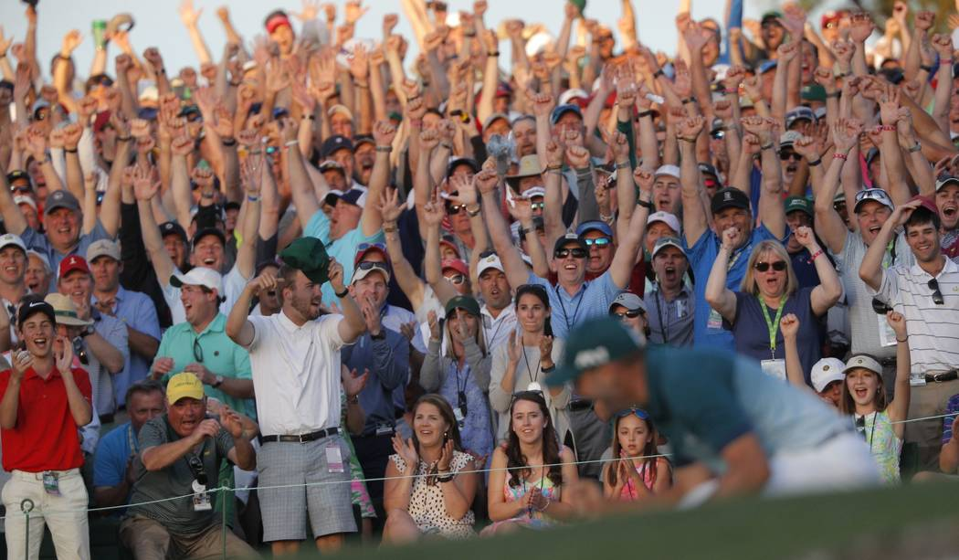 Patrons cheer as Sergio Garcia of Spain (R) celebrates winning the Masters with a putt on the 18th green during a playoff against Justin Rose of England in the final round of the 2017 Masters golf ...