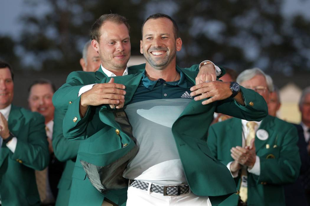 Sergio Garcia of Spain is presented the green jacket by last year's champion, Danny Willett of England, after Garcia won the 2017 Masters golf tournament in a playoff at Augusta National Golf Club ...
