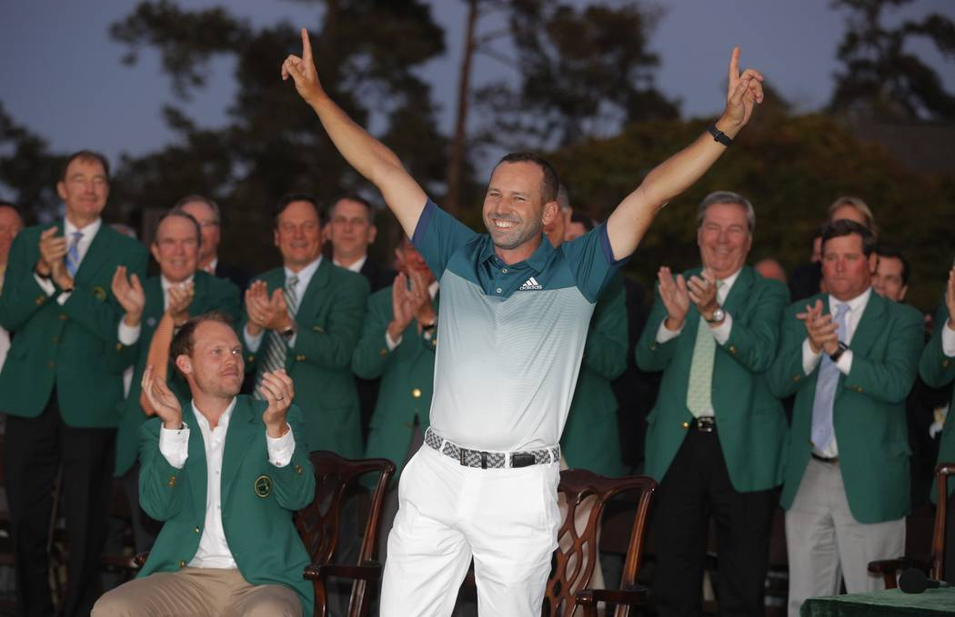 Sergio Garcia of Spain smiles next to the 2016 champion, Danny Willett of England (L), as he waits to receive his green jacket during the traditional ceremony after Garcia won the 2017 Masters gol ...