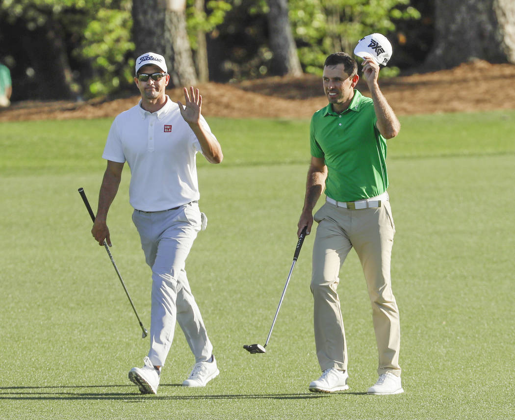 Charl Schwartzel, of South Africa, and Adam Scott of Australia, walk up the 18th hole during the final round of the Masters golf tournament Sunday, April 9, 2017, in Augusta, Ga. (AP Photo/David J ...