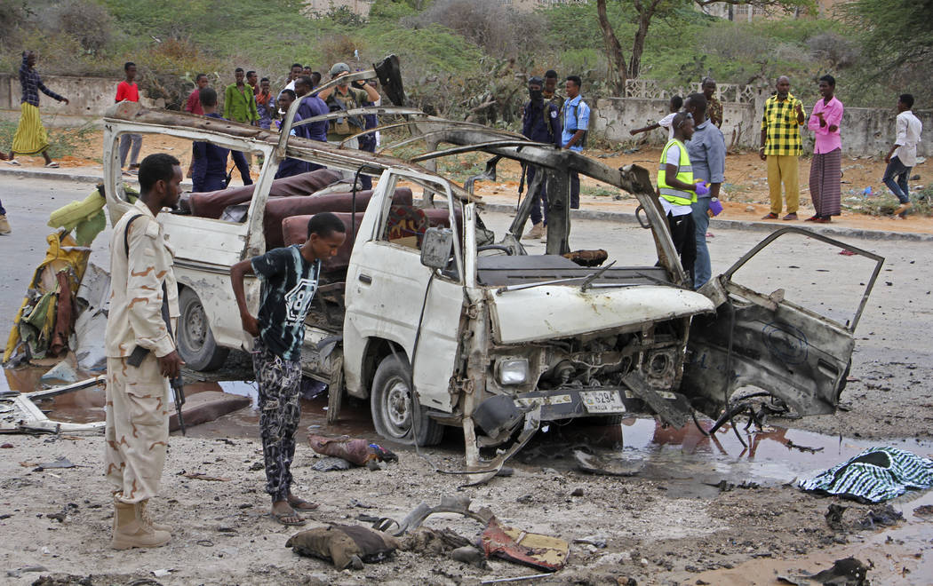 A Somali soldier, left, stands by the wreckage of a passing minibus that was destroyed in a suicide car bomb attack near the defense ministry compound in Mogadishu, Somalia Sunday, April 9, 2017.  ...