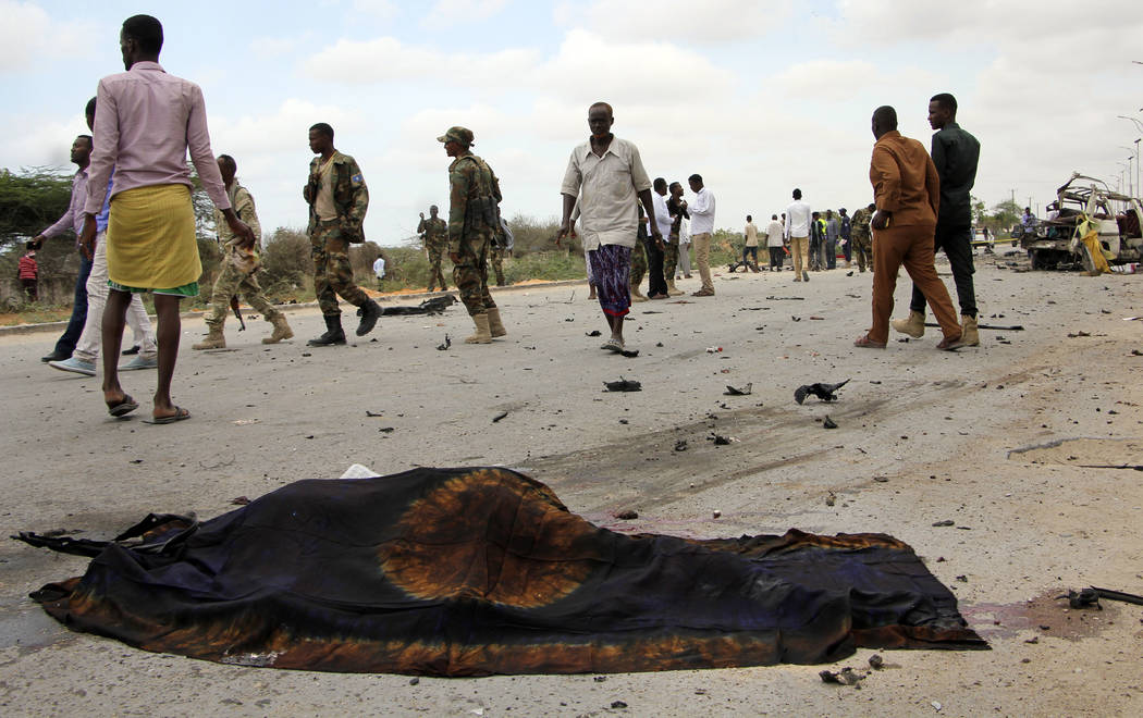 Soldiers and others pass by the covered dead body of a man killed in a suicide car bomb attack, near the defense ministry compound in Mogadishu, Somalia Sunday, April 9, 2017. Somalia's new milita ...