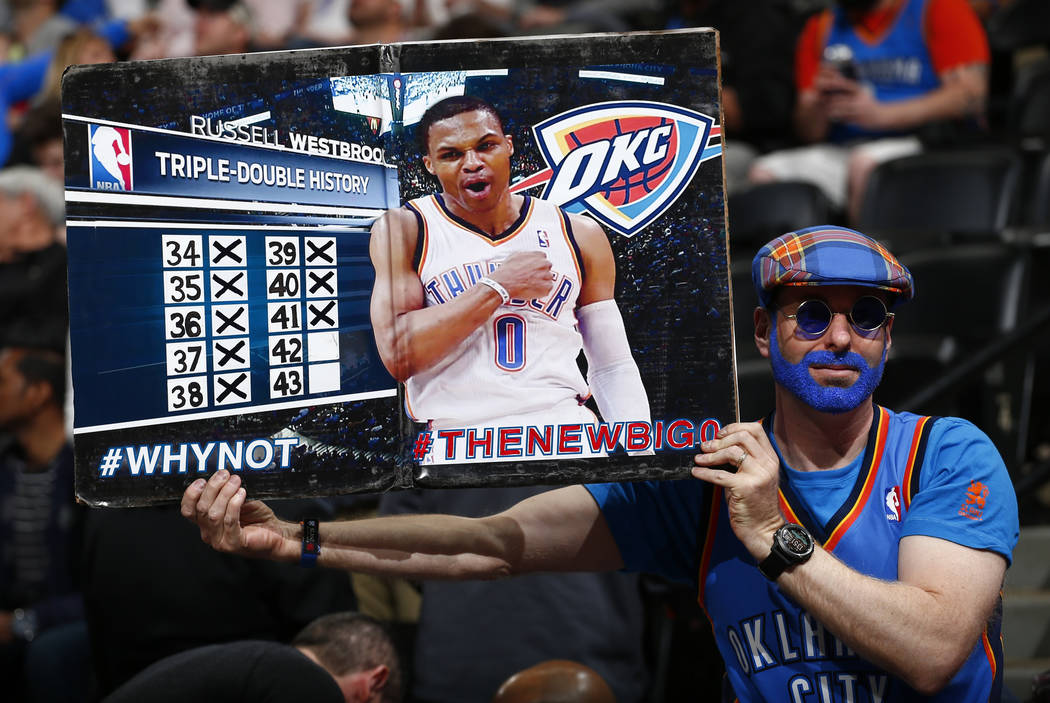 An Oklahoma City Thunder fan shows the Russell Westbrook triple double history board during the first half of a basketball game against the Denver Nuggets Sunday, April 9, 2017, in Denver. (Jack D ...