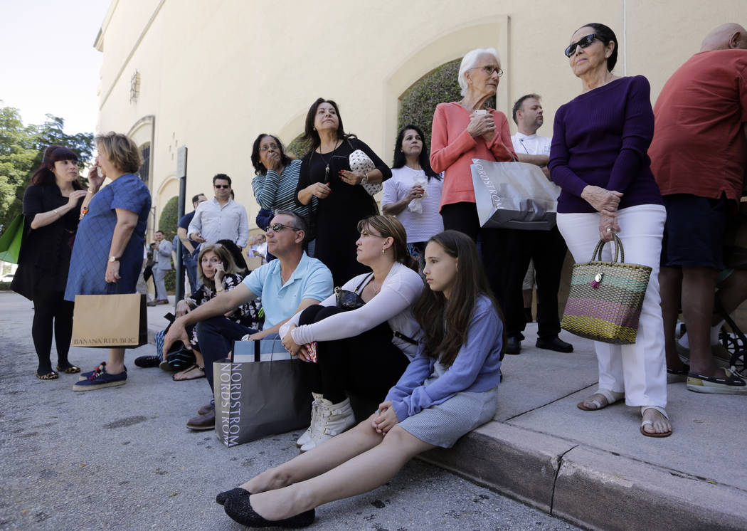 Shoppers Roman Lugo, seated, left, Siuris Rodriguez, center, and Chelsea Lugo, right, sit on the pavement after being evacuated from the Shops at Merrick Park after a shooting, Saturday, April 8,  ...