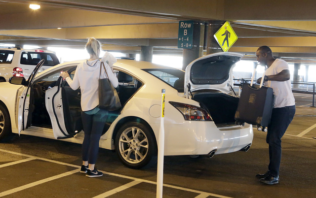 Ride-hailing company Uber driver, who refused to give his name, loads luggage into his vehicle as he picks a rider up from McCarran International Airport at Terminal 1 Thursday, Oct. 20, 2016. Biz ...